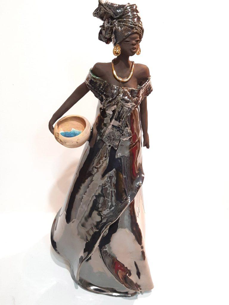 sculpture d'une femme africaine portant un vase d'eau